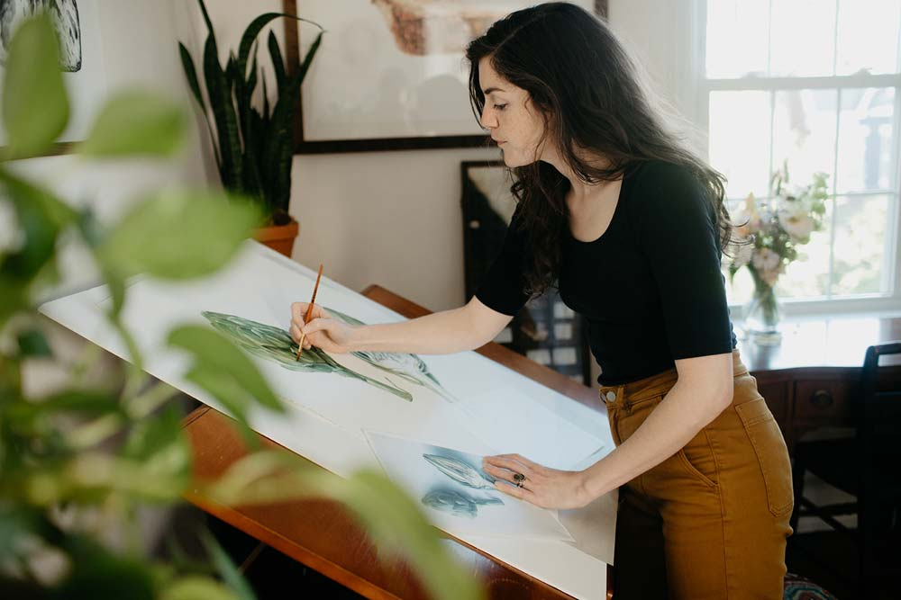 woman in an art room surrounded by plants while painting
