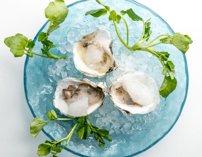oysters on ice in a glass bowl