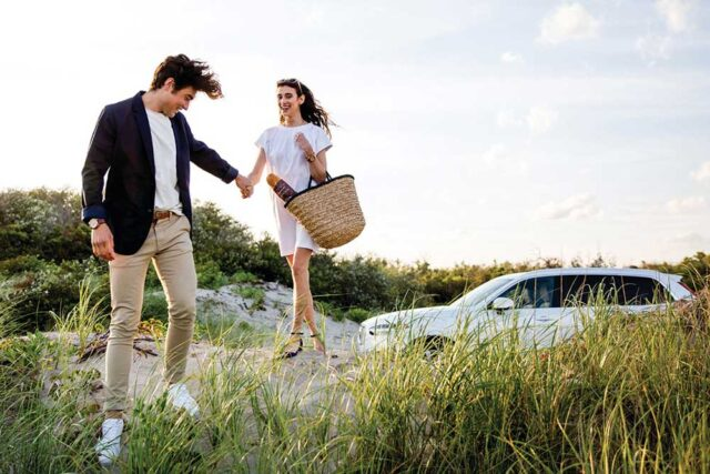 grass foreground with couple and white Volvo in the background