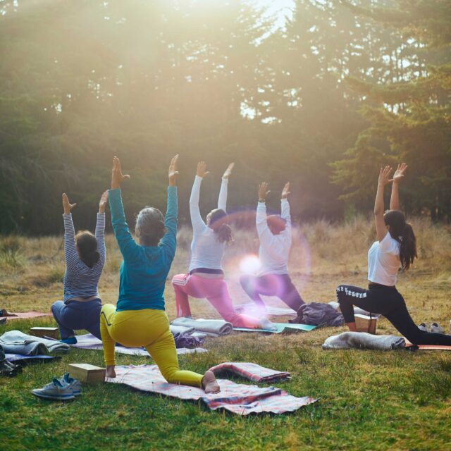 group of women doing yoga with trees in the background