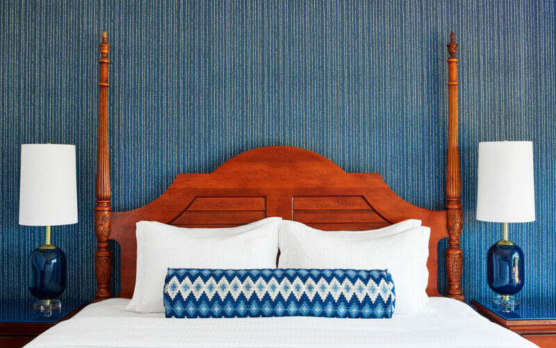 white linen on king size bed with wooden headboard